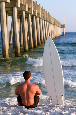 beach front: Surfer sits watching the waves in the sand at the beach next to his surfboard in front of a fishing pier.