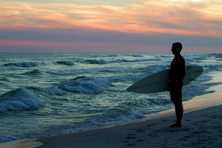 pensacola: Surfer stands at the coastline holding his surfboard and watching the waves at sunset.