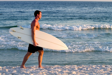 Surfer carrying his surfboard walks along the beach.