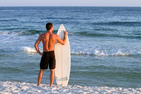 pensacola: Young adult surfer stands by the shoreline holding his surfboard looking out into the sea.