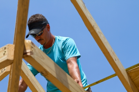 rafters: Carpenter uses a tape measure to calculate the length of the next sheathing board to cut for the roof.