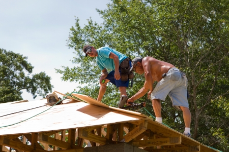 rafters: Carpenters use a pneumatic nail gun to secure plywood sheathing to the truss rafters of a home. Stock Photo