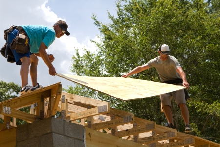 Two carpenters place plywood onto trusses to be nailed down for the roof. Stock Photo - 14000194