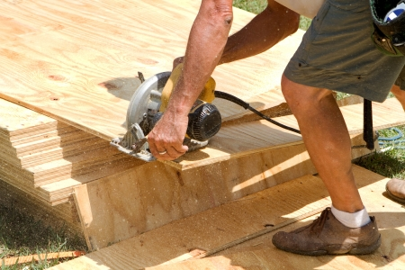 Sawdust fills the air as a carpenter uses a electric powered circular saw to cut a sheet of plywood at a construction site