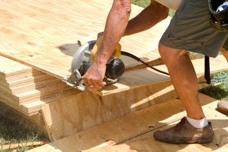 Zaagsel vult de lucht als timmerman maakt gebruik van een elektrisch aangedreven cirkelzaag met een blad van triplex gesneden op een bouwplaats