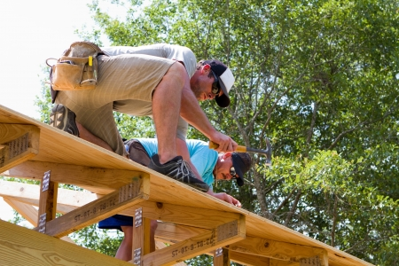 Two carpenters nail plywood sheathing to a truss roof on a new home at a construction job site Stock Photo - 14171772