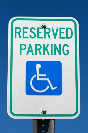 Disabled and handicapped reserved parking sign against a blue sky  photo