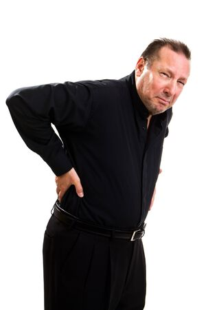 spinal adjustment: Elderly man holds his back and bends over in pain and makes a grimacing facial expression.