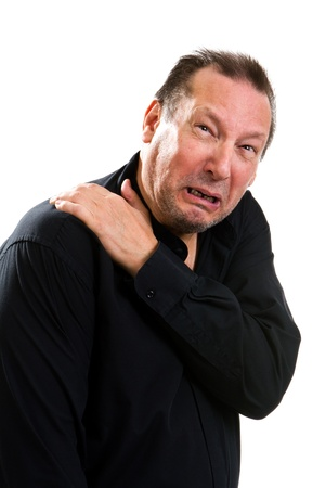 distressing: Elderly man suffering with a hurting shoulder rubs it with his hand and makes a painful expression. Stock Photo