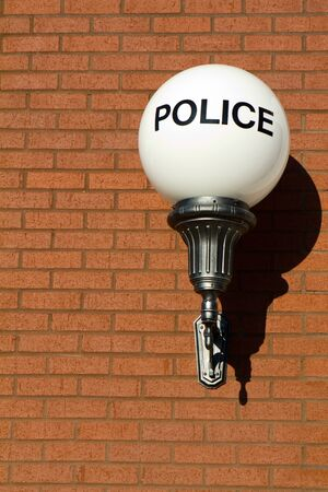 police station: Old fashioned vintage police sign on a globe light hangs on a brick wall outside a retro designed city police station