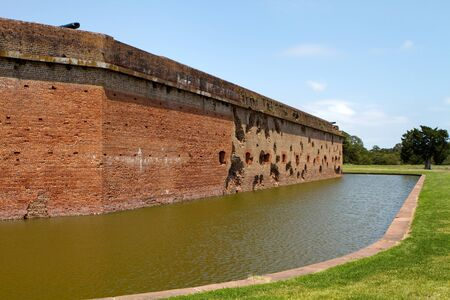 tybee island: Moat and exterior walls of Fort Pulaski National Monument on Cockspur Island in the Savannah River, Georgia, USA. Holes were made by Union canon fired from Tybee Island during the Civil War.