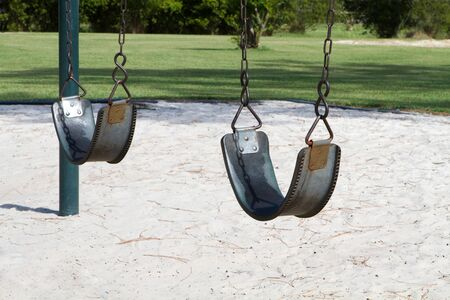 Empty swings in a vacant playground to be used as a conceptual image for abused, abducted or missing children. photo