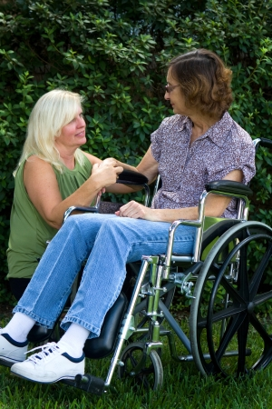Caregiver tries to comfort an elderly disabled woman in a wheelchair.