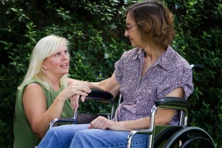gente pobre: Mujer cuidadora consuela a un paciente discapacitado en silla de ruedas confinado. Foto de archivo