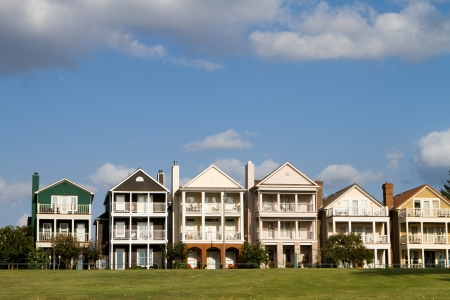row of houses: Upscale townhomes for the wealthy built on a grass hill in a row against a cloudy blue sky in Memphis, Tennessee