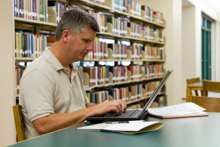 Middle-aged college student types on a laptop in the library  Stock Photo