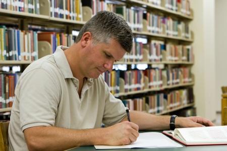 researches: Mezza et�, studente di college che � tornato al college per proseguire la sua istruzione e la formazione, ricerche in biblioteca
