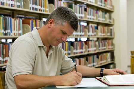 Middle-aged college student who has gone back to college to further his education and training, researches in the library