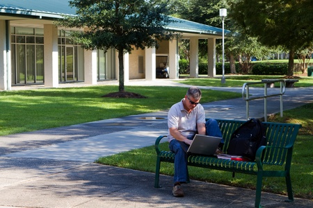 retraining: Middle aged student works on his laptop while sitting on a bench on a university campus outdoor area