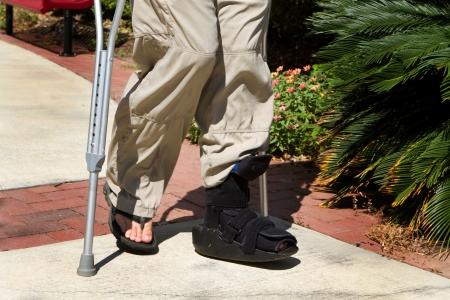 偶発的な損傷後歩く彼を助けるため足と足首の支柱と共に松葉杖を使う 写真素材