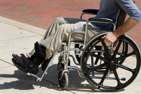 Injured man with a broken foot pushes himself along in his wheelchair  Foto de archivo