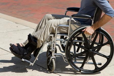 accessibilit�: Uomo ferito con un piede rotto si spinge oltre nella sua sedia a rotelle Archivio Fotografico
