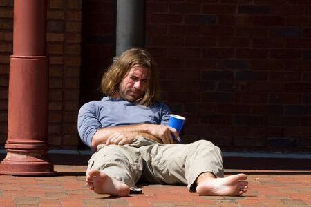 drunkard: Man under the influence of drugs and alcohol leans against a pole sleeping it off on a city brick sidewalk