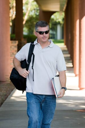 more mature: Mature adult student on campus walks to class carrying his books and backpack as he goes back to college for more education and training  Stock Photo