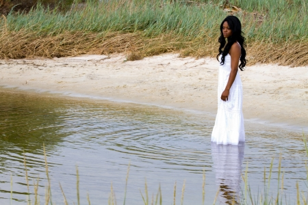standing water: Lonely African American woman stands downcast in shallow water with a sad pensive look on her face