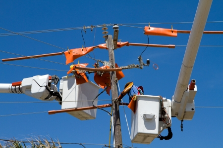 utility pole: Utility workers repair power lines from the safety of a bucket boom