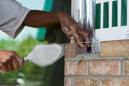 African American worker lays a row of bricks using cement mortar and a trowel at a new house under construction  Imagens