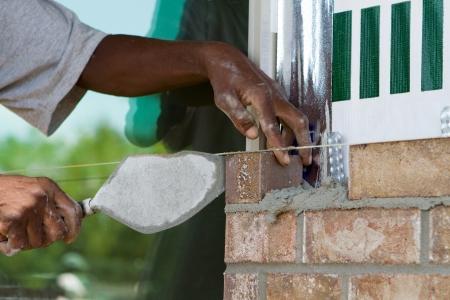 Afro-Amerikaanse arbeider legt een rij stenen met behulp van cement mortel en een troffel op een nieuw huis in aanbouw
