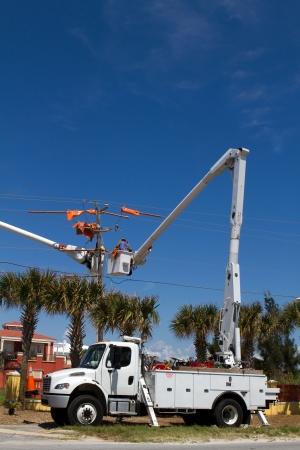 camion grua: Trabajo instalador de l�neas el�ctricas en l�neas de alta tensi�n desde la seguridad de un cubo en un cami�n recogedor de la cereza Foto de archivo