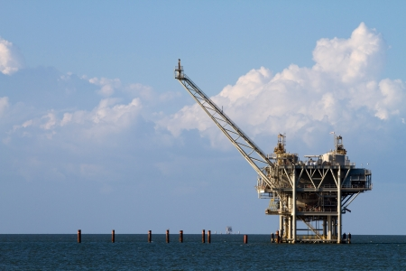 Gulf of Mexico oil rig against a cloudy blue sky