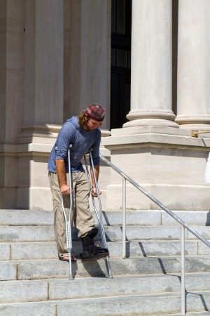 crippled: Man on crutches and wearing an ankle cast makes his way down concrete steps in front of a county courthouse  Stock Photo