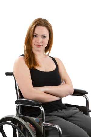 Woman sits confidently in wheelchair with arms crossed. photo