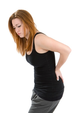 Vrouw met pijn in haar rug buigt zich over wrijven de plek om het ongemak te verlichten.