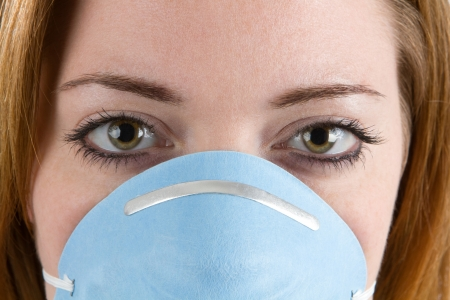 dust mask: Close up of woman face wearing a filter mask or facemask. Stock Photo