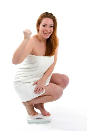 Happy woman smiling about the results on the bathroom scale of the amount of her losing weight. Stok Fotoğraf