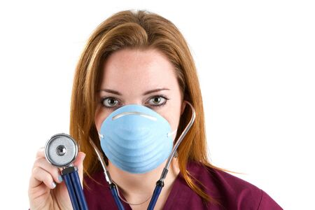 Female nurse wearing scrubs and a surgical mask holds a stethoscope. photo