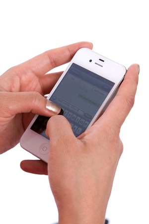 Womans hands hold a cell phone while texting a message. Editorial
