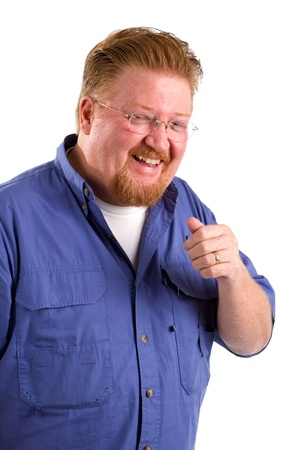 chuckles: Red haired man with mustache and beard laughs and gestures with his hand. Stock Photo