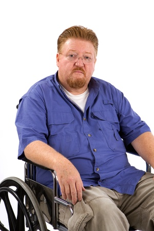 impaired: Overweight disabled man sits in a wheelchair with a sad expression on his face. Stock Photo