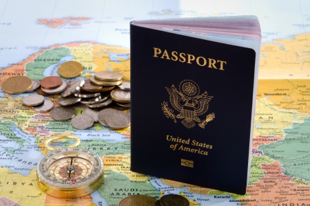 european exchange: USA passport, compass and foreign coins sit on a map of Europe for an international travel concept.