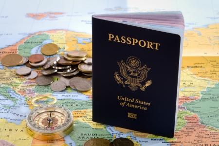 USA Reisepass, Kompass und ausländische Münzen sitzen auf einer Karte von Europa für eine internationale Reise-Konzept. Standard-Bild - 17689491