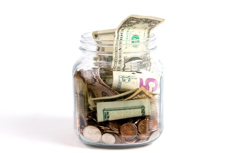 US dollars and coins fill a glass tip jar with money.