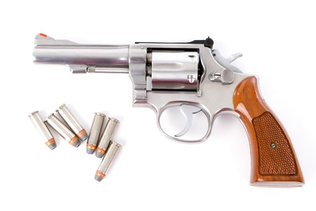 A chrome  38 police special revolver handgun with six hollow point bullets on a white background  photo