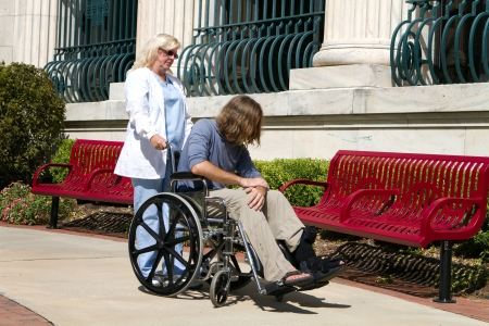 psychopathy: Nurse caregiver looks after a disabled psychopathic patient outside a state hospital facility for the mentally insane