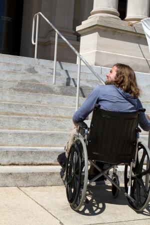 persona en silla de ruedas: Hombre discapacitado en silla de ruedas busca una rampa para acceder a una entrada del edificio p�blico