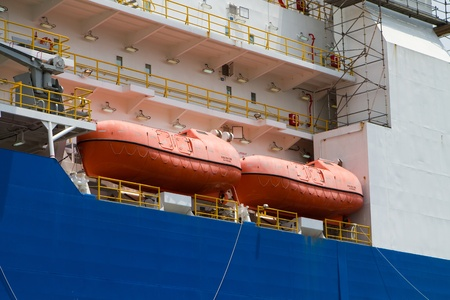 raft: Orange survival lifeboats sit on the deck of an industrial ship  Stock Photo